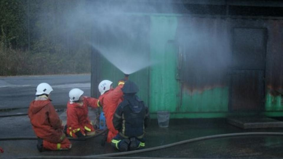 Three firefighters being trained by an instructor in nozzle technique.
