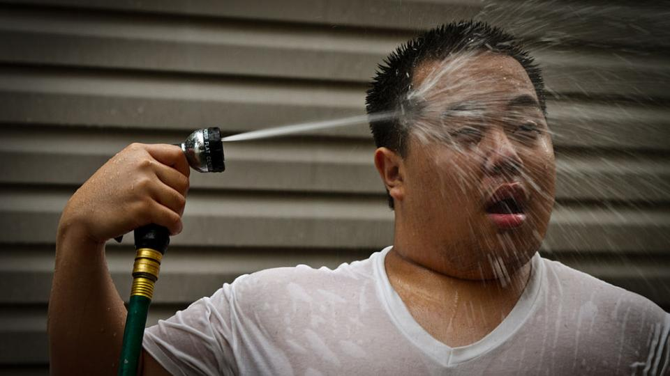 Man cooling down with water from a hose. Photo: Wikipedia Commons License