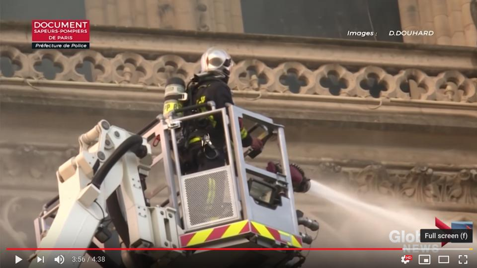 A Paris firefighter in a ladder basket working to extinguish at Notre Dame. Photo screen shot from Paris Fire Brigade Video.