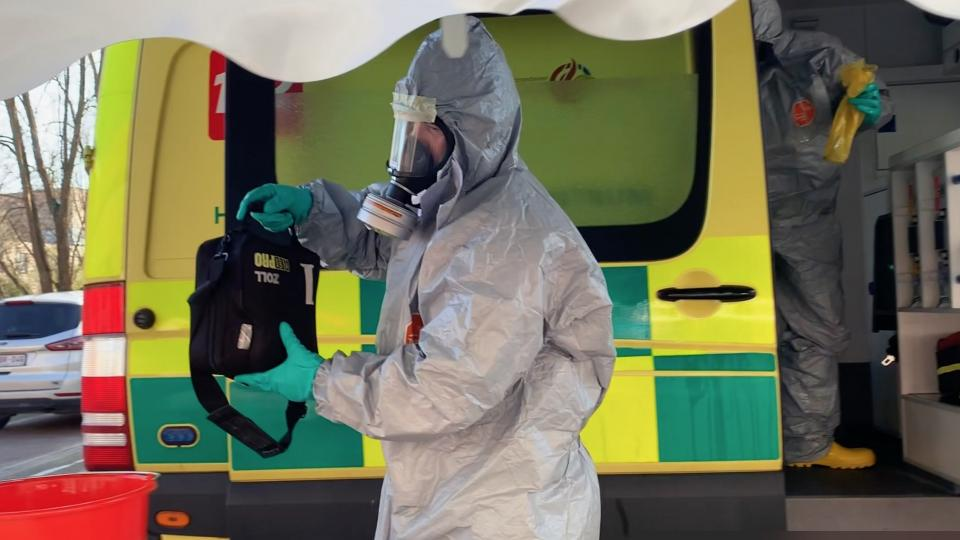 EMS staff in a hazmat suit. Screen shot from a Belgian instructional video.